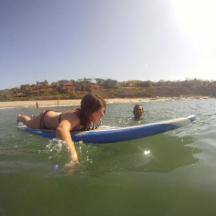 girl paddling during surf lesson in puerto escondido